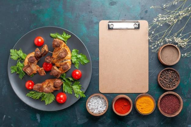 Вид сверху нарезанное приготовленное мясо с зеленью, помидорами черри и приправами на синем фоне Бесплатные Фотографии