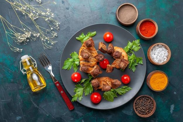上面図スライスした調理済み肉と緑のチェリートマトオイルと青の背景に調味料 無料写真