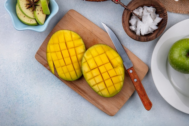 Top view of sliced fresh mango on a wooden kitchen board with knife and chopped apples in a white bowl and pulps of coconut in a wooden bowl on white surface Free Photo