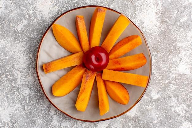 Vista dall'alto di pesche fresche a fette all'interno del piatto su superficie bianca chiara Foto Gratuite