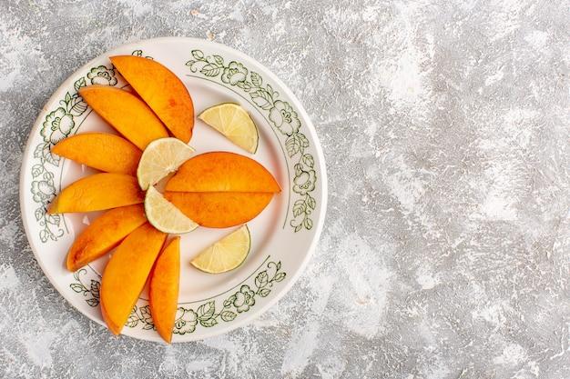 Vista dall'alto di pesche fresche a fette all'interno del piatto con limoni sulla superficie bianca chiara Foto Gratuite