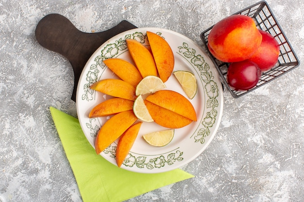 Top view of sliced fresh peaches inside plate with lemons on white surface Free Photo