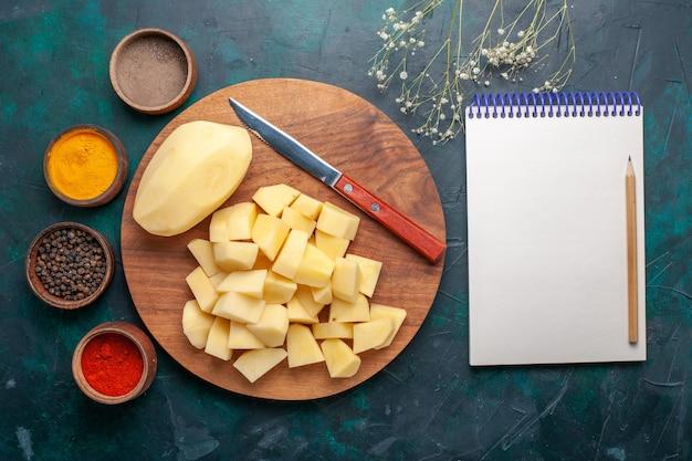 Vista dall'alto di patate fresche a fette con condimenti e blocco note su sfondo blu scuro Foto Gratuite