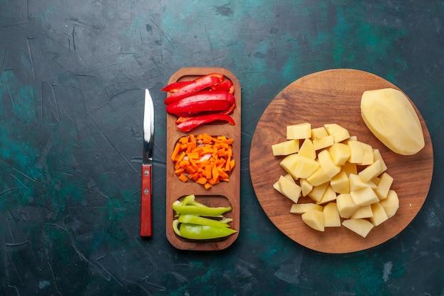 紺色の背景にスライスしたピーマンとスライスした新鮮なジャガイモの上面図 無料写真