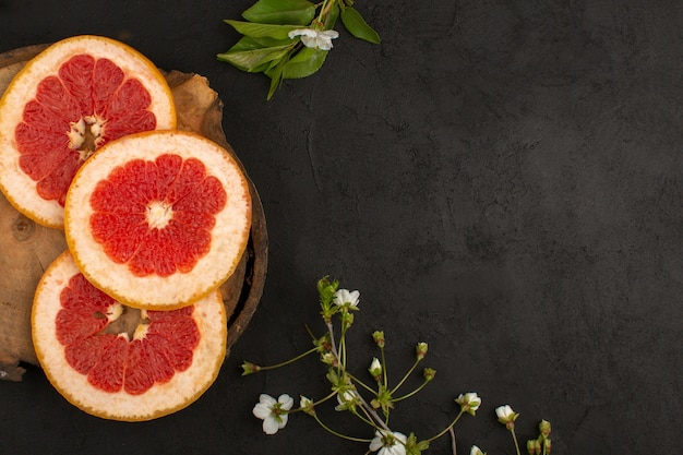 Top view sliced grapefruits rings mellow juicy on the dark background Free Photo