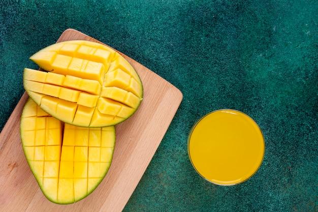 Вид сверху нарезанный манго на доске со стаканом апельсинового сока на зеленом Бесплатные Фотографии