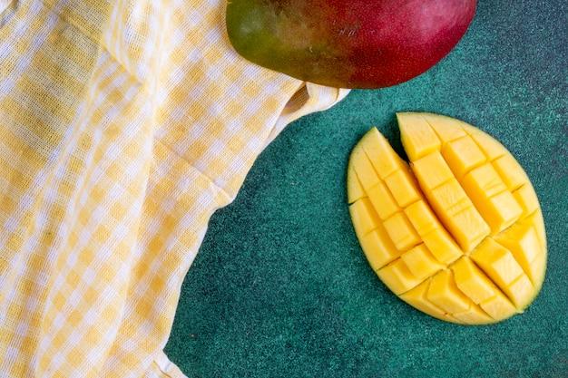 Вид сверху нарезанный манго с желтым кухонным полотенцем на зеленом Бесплатные Фотографии