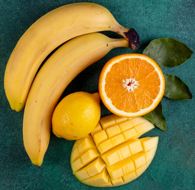 Вид сверху нарезанный манго с бананами половиной апельсина и лимоном на зеленом Бесплатные Фотографии