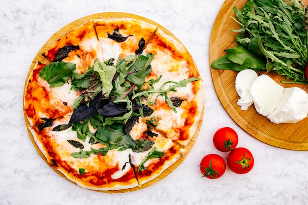 Top view of sliced margherita pizza topped with rocket Free Photo