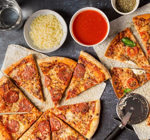 Вид сверху нарезанная пицца с томатным соусом и моцареллой Бесплатные Фотографии