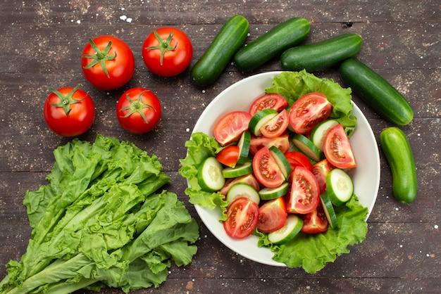 Pomodori affettati vista superiore con i cetrioli dentro il piatto bianco con insalata verde su marrone, insalata fresca di verdure dell'alimento Foto Gratuite