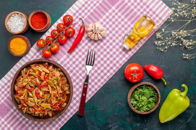 Vista dall'alto di farina di verdure a fette con diversi condimenti su sfondo blu scuro Foto Gratuite