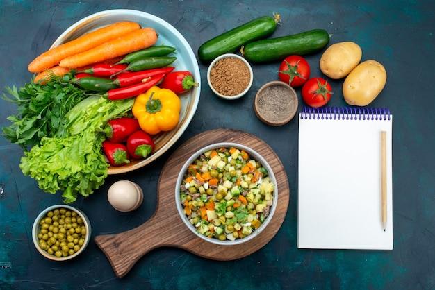 Vista dall'alto insalata di verdure a fette condita con fette di pollo all'interno del piatto con verdure fresche sulla scrivania blu scuro Foto Gratuite