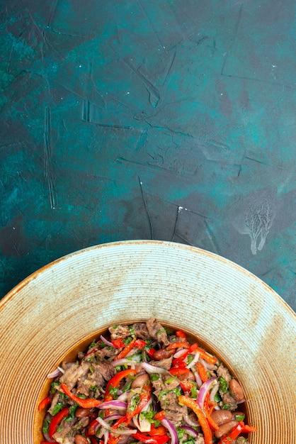 Vista dall'alto di insalata di verdure a fette con carne riattaccata all'interno della piastra marrone su sfondo blu scuro insalata di cibo pasto foto di verdure Foto Gratuite