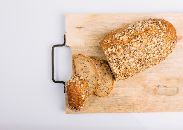 Top view of sliced wholegrain bread on chopping board over white background Free Photo