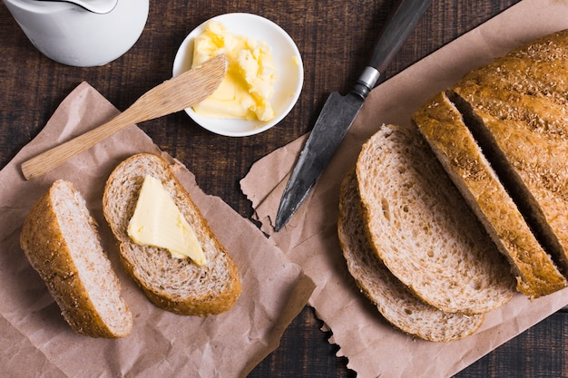 Vista dall'alto fette di pane con burro e coltello Foto Gratuite