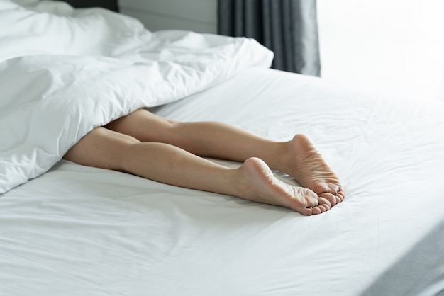 Top view of a slim woman legs. bare legs of a young woman sleeping on her bed at home. Premium Photo
