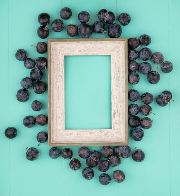 Vista dall'alto delle piccole prugnole astringenti globose scure su sfondo blu con spazio di copia Foto Gratuite