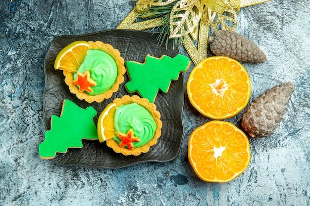 上面図黒いプレートに緑のペストリークリームクリスマスツリービスケットと小さなタルトクリスマス飾りは灰色のテーブルにオレンジをカット 無料写真