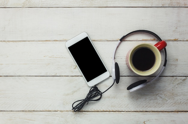 top view smartphone and headphones with coffee cup Free Photo
