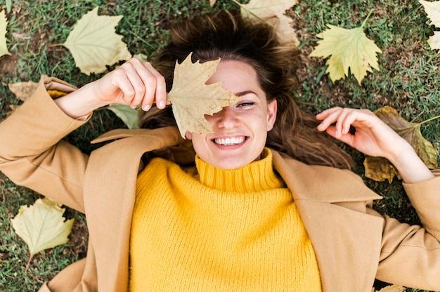 Вид сверху смайлик молодая женщина, оставаясь на земле рядом с осенними листьями Premium Фотографии