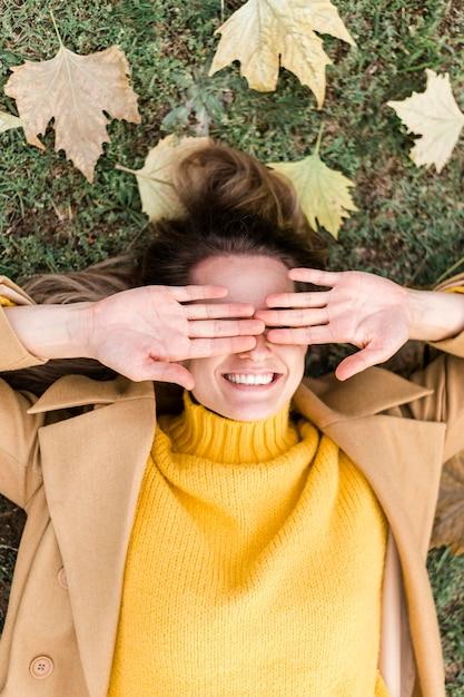 Вид сверху смайлик молодая женщина, оставаясь на земле Бесплатные Фотографии