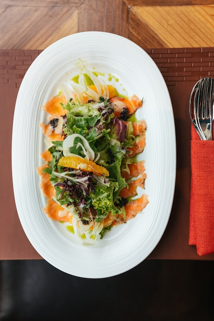 Top view of smoked salmon pomelo salad include green oak, red leaf lettuce and onion. Premium Photo