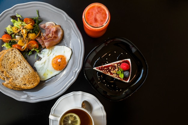 Top view of smoothie; cheesecake; tea; toast; salad; bacon; fried egg and toast on gray plate over black background Free Photo