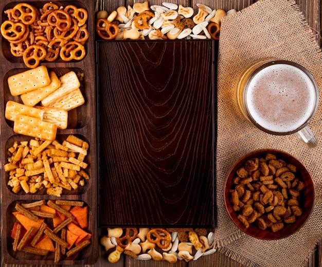トップビュースナックビールハードチャックミニブレゼル塩味クラッカーフィッシュクラッカーチップと木製の背景にコピースペースを持つ白いヒマワリの種 無料写真