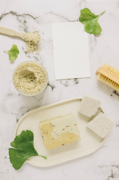 Top view of soap; salt; pumice stone; brush; ginkgo leaf and blank card on marble backdrop Free Photo
