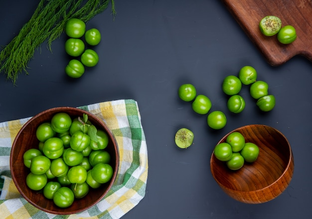Top view of sour green plums in wooden bowls and wooden cutting board with sliced plums on black table Free Photo
