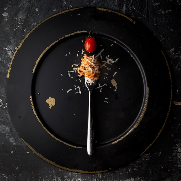Top view spaghetti with fork and tomato and ricotta cheese in round black plate Free Photo