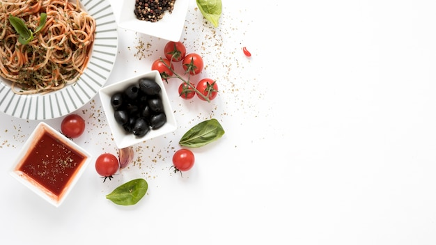 Top view of spaghetti with olive; tomato; basil leaf; herbs on white backdrop Free Photo