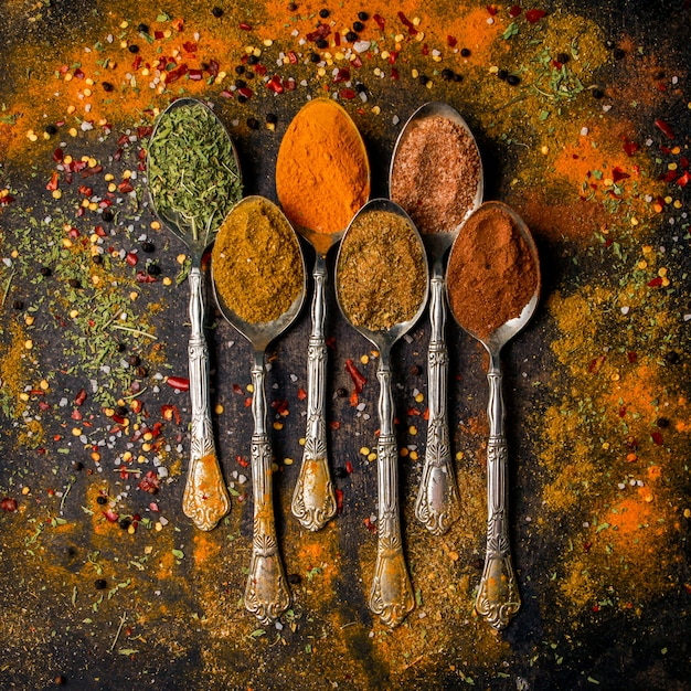 Top view spice with pepper and cinnamon and turmeric in spoon Free Photo
