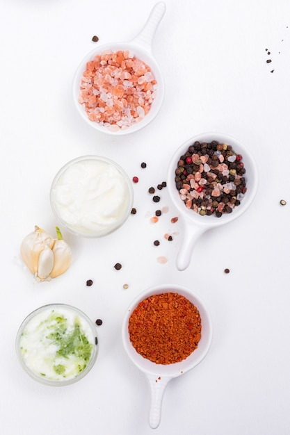 Top view spices salt papper with garlic and white yogurt on white  vertical Free Photo