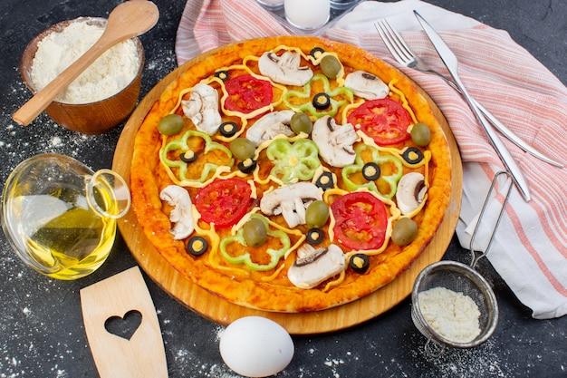 Vista dall'alto pizza ai funghi piccanti con pomodori rossi peperoni olive tutte affettate all'interno con olio sulla pasta della pizza sfondo scuro Foto Gratuite