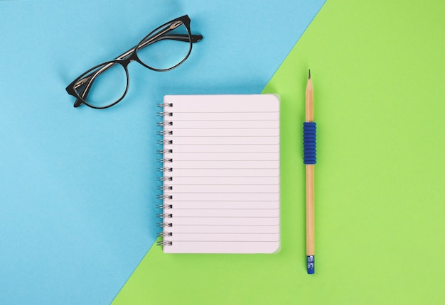 Top view of spiral notepad, wooden pencil and glasses on blue-green background. Premium Photo