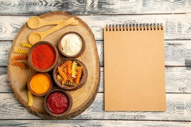 灰色の机の上にさまざまな調味料を使った上面図スパイラルパスタ 無料写真