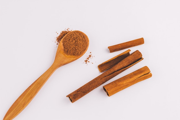 Top view of a spoon of sandal wood with cinnamon  on light  background Premium Photo
