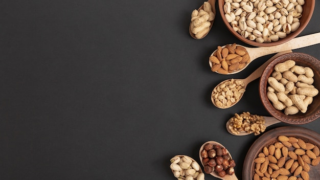 Top view of spoons and bowl with assortment of nuts and copy space Premium Photo