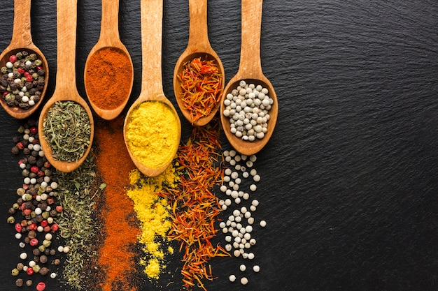 Top view spoons with spices powder and spread besides Free Photo