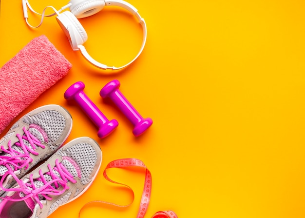 Top view sports attributes on yellow background Free Photo