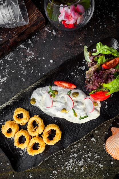 上面のイカリングとバターのソースとトレイに新鮮な野菜サラダ 無料写真