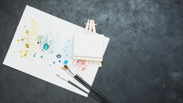 Top view of stained drawn paper with paint brush and mini blank easel Free Photo