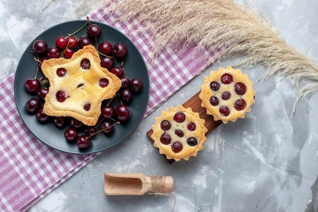 Вид сверху торт в форме звезды вместе с вишневыми пирогами и свежей вишней на светлом столе торт пирог испечь фруктовый цвет Бесплатные Фотографии