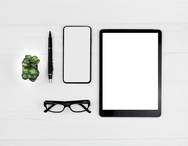 Top view stationery arrangement on blue background with tablet and phone mock-up Free Photo