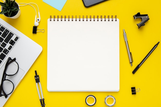 Top view stationery arrangement on yellow background with empty notepad Free Photo