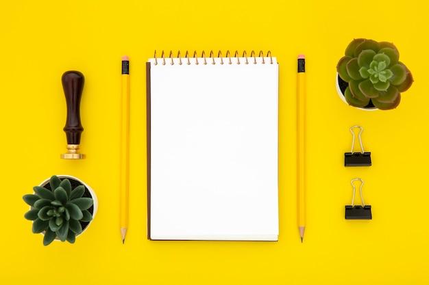 Disposizione della cancelleria di vista superiore su sfondo giallo Foto Gratuite