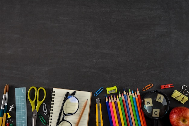 Top view of stationery or school supplies with books, color pencils, calculator, laptop, clips and red apple on chalkboard background. Premium Photo