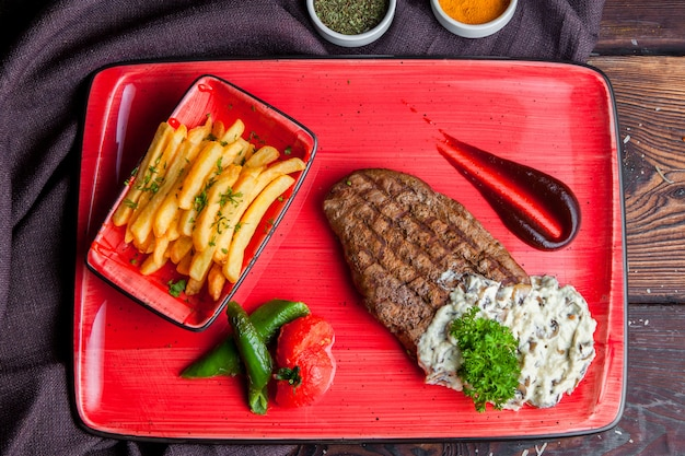 Top view steak steak with_fried potato sauce, spices on a red plate Free Photo